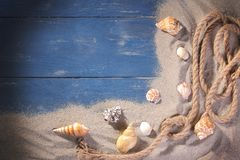 Une corde de mer avec beaucoup de différentes coquilles de mer sur le sable de mer sur un fond en bois bleu photos stock