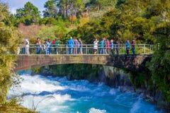 Une couronne des personnes au-dessus du pont appréciant la vue du Huka puissant tombe sur la rivière de Waikato près du nord de T photographie stock libre de droits