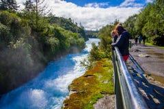 Une couronne des personnes au-dessus du pont appréciant la vue du Huka puissant tombe sur la rivière de Waikato près du nord de T images libres de droits