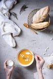 Une crème sure se renversante de personne dans une soupe jaune sur la table image libre de droits