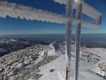Une croix de congélation sur le dessus des montagnes libanaises du nord avec une église pour le saint se marient derrière Photos stock