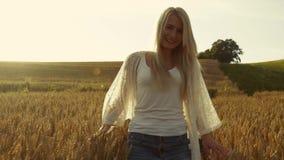 Une croix de marche de fille insouciante et mignonne le champ du blé d'or, le soleil descend Belles couleurs Calme, joie clips vidéos