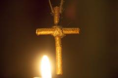 Une croix en bois contre les flammes de la bougie Images libres de droits