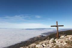 Une croix en bois sur la montagne de Subasio, avec une mer de bel de brouillard Image stock