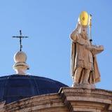 Une croix et un sclupture sur l'église de la rue Blasius Photographie stock libre de droits