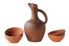 Une cruche de vin et un ensemble de tasses de terre cuite d'argile Photo libre de droits