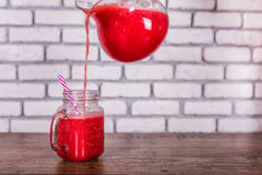 Une cruche versant le smoothie rouge fraîchement mélangé de fruit dans le pot en verre avec la paille Foyer sélectif Concept de m Photo libre de droits