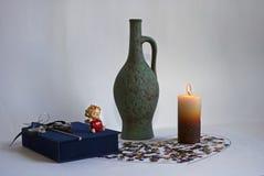 Une cruche verte et une bougie allumée Photos stock