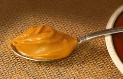 Une cuillère de beurre d'arachide au-dessus d'un plancher de sac Images libres de droits