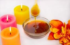 Une cuillère en bois avec du sucre liquide, pour l'epilation Avec du miel liquide Plan rapproché Aromatherapy, bougies photo libre de droits