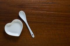 Une cuillère se trouve à côté d'un plat en forme de coeur blanc sur une table en bois Plats élégants en céramique sur un fond d'é photographie stock