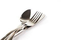 Une cuillère, une fourchette et un couteau empilés sur un fond blanc Photos stock