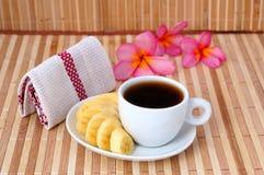 Une cuvette de café avec la banane images stock