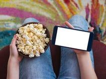 Une cuvette de maïs éclaté et d'un téléphone avec le fond de coupure sur les genoux du ` s d'enfant Images stock