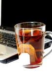 Une cuvette de thé et d'un ordinateur portatif. photo libre de droits