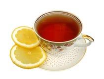 Une cuvette de thé et parts de citron Images stock
