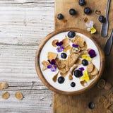 Une cuvette en bois avec le petit déjeuner fait maison : yaourt, grains entiers, myrtilles, fleurs comestibles d'un alto de jardi Photographie stock