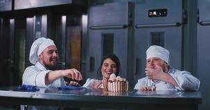 Une dame élégante portant un uniforme de cuiseurs enlève ses gants et deux hommes de boulanger près de elle font la même chose, i banque de vidéos