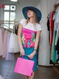 Une dame attirante dans un chapeau verrat-débordé par bleu fait des achats sur un fond de boutique d'habillement Concept de vente photos libres de droits