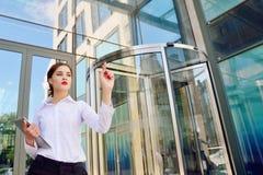 Une dame d'affaires avec un comprimé dans sa main clique sur dessus un Di virtuel image stock