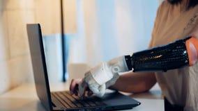 Une dame dactylographie sur son ordinateur portable avec un sain et les bras robotiques clips vidéos