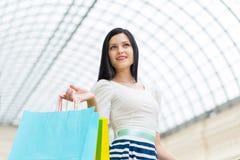 Une dame de sourire heureuse avec beaucoup de paniers colorés des boutiques de fantaisie Images stock
