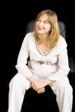 Une dame enceinte s'asseyant sur une présidence noire photographie stock