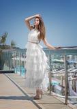 Une dame magnifique et jeune dans la robe blanche et sur des talons hauts sur un balcon du ` s d'hôtel Charme dans une robe éléga Photos libres de droits