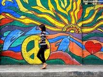 Une dame marchant après un art de mur de rue Photographie stock libre de droits