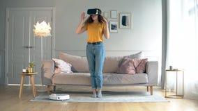 Une dame met sur des VR-verres dans la chambre avec un aspirateur robotique banque de vidéos