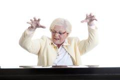 Une dame plus âgée en jaune jouant le piano Photos libres de droits