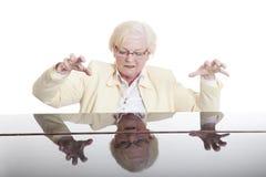 Une dame plus âgée en jaune jouant le piano Image libre de droits
