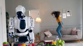 Une dame saute sur un sofa tandis qu'un robot fait cuire banque de vidéos