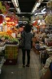 Une dame se tient avec elle de nouveau à l'appareil-photo dans une île de marché de Sheung Shui Photographie stock libre de droits