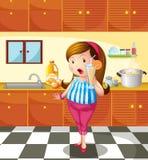 Une dame tenant un jus d'orange à l'intérieur de la cuisine Photographie stock