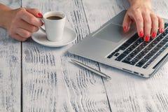 Une dame tient le café dans sa main au bureau de PC photographie stock libre de droits
