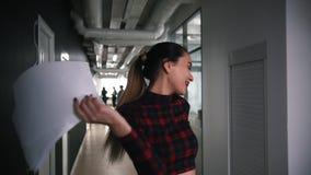 Une danse enthousiaste de femme d'affaires en journal de couloir de bureau, de chant et de lancement banque de vidéos