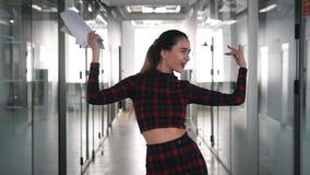 Une danse enthousiaste dr?le de femme d'affaires dans le couloir de bureau banque de vidéos