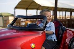 Une direction souriante de garçon dans le véhicule de jouet Image libre de droits