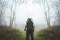Une double exposition d'une figure à capuchon fantasmagorique regardant deux manières Dans un brumeux, forêt mystérieuse d'hiver photographie stock libre de droits