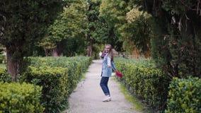 Une douce fille aux cheveux longs et aux épines bleues en imperméable s'est étendue les bras sur le chemin du parc banque de vidéos