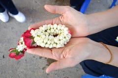 Une eau sacrée faite d'eau douce écartant par des pétales de fleur, utilisé pour verser sur la main plus ancienne du ` s pendant  images libres de droits