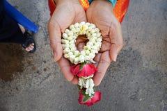 Une eau sacrée faite d'eau douce écartant par des pétales de fleur, utilisé pour verser sur la main plus ancienne du ` s pendant  image stock