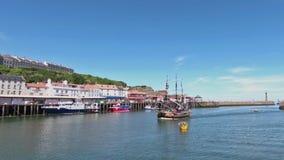Une embarcation de plaisance arrive dans le port de Whitby, Angleterre banque de vidéos