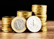 Une euro pièce de monnaie et nous pièce de monnaie de quart de dollar Photos stock
