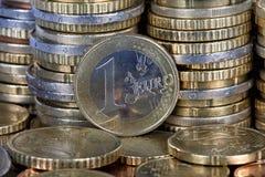 Une euro pièce de monnaie située devant plus de pièces de monnaie Photo libre de droits