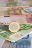 Une euro pièce de monnaie sur d'euro billets de banque Images stock