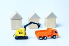 Une excavatrice de chenille de jaune charge un camion à benne basculante orange dans la perspective des maisons construites du `  photo stock