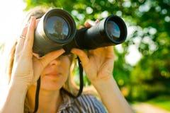 Une exploratrice de femme utilise les jumelles noires - extérieures images stock