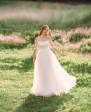 Une fée aimable dans une robe blanche danse dans un dédouanement de belles fleurs roses princesse gracieuse liberté et images libres de droits
